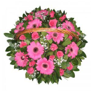 Flower arrangement in fuchsia shade in basket with handle
