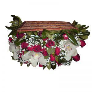 Ανθοσύνθεση σε μπαουλάκι  με κόκκινα τριαντάφυλλα, άσπρες ορχιδέες (σιμπίτιουμ) και γυψόφυλλο