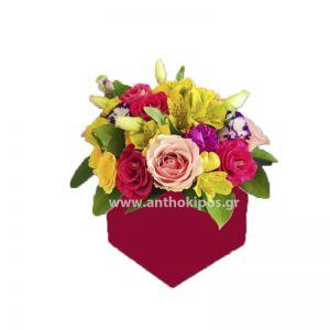 Πολύχρωμη σύνθεση λουλουδιών σε κόκκινο τετράγωνο κουτί